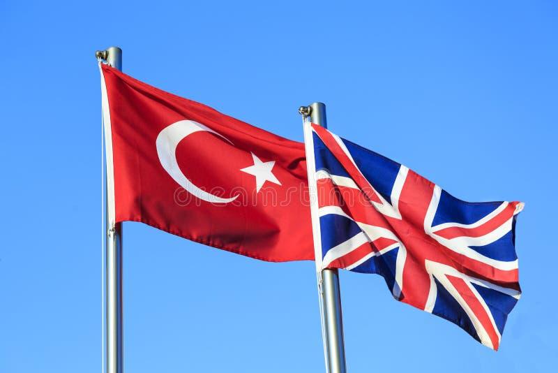 在蓝天背景的土耳其和英国旗子 免版税图库摄影