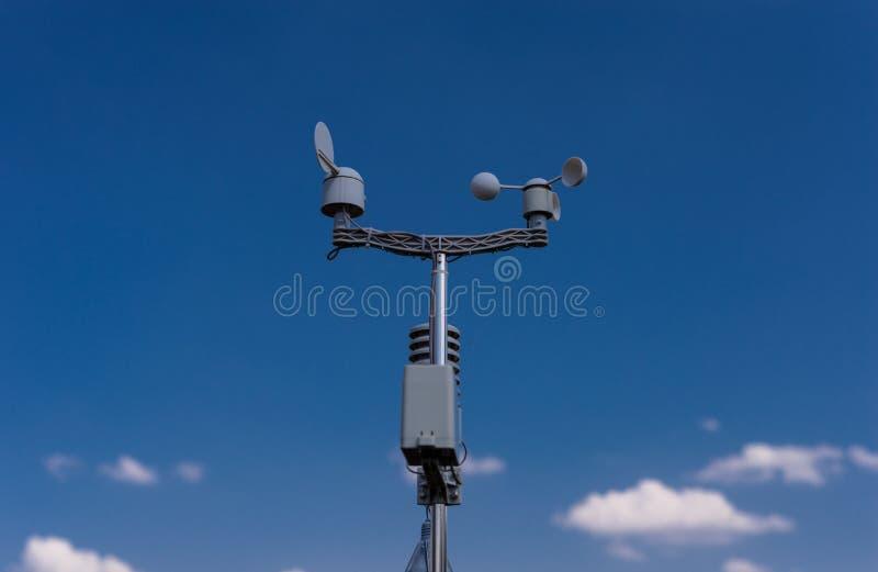 在蓝天背景的家庭气象台与太阳的在云彩后 温度、湿气和风dir的测量 免版税图库摄影