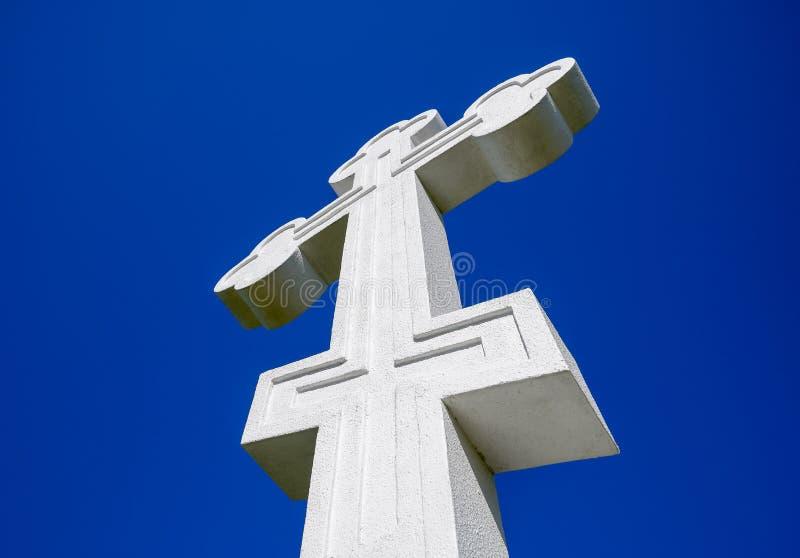 在蓝天背景的白色正统基督徒十字架 免版税库存图片