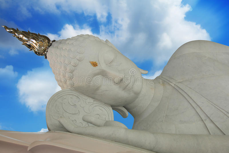 在蓝天背景的睡觉大理石菩萨雕象 图库摄影