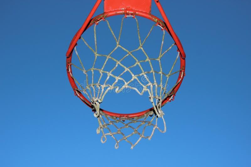 在蓝天背景的被隔绝的篮球网 库存照片