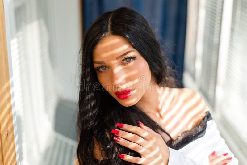 在蓝眼睛性感的深色的女孩美丽的少妇的特写镜头画象有获得红色的唇膏的肉欲上看照相机的乐趣 免版税图库摄影
