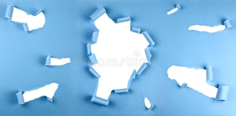 在蓝纸的被撕毁的孔 免版税图库摄影