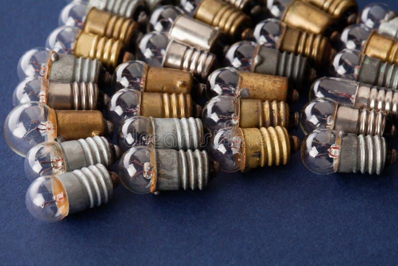 在蓝纸背景设置的电灯泡 五颜六色的金古铜和银葡萄酒灯 宏观看法浅深度  库存图片