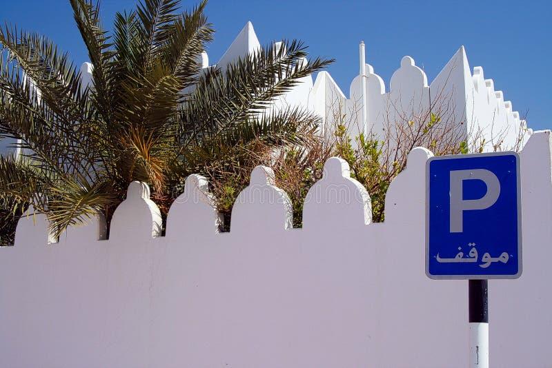 在蓝色停放的标志的看法与白色城垛墙壁和棕榈树,阿曼 免版税库存照片