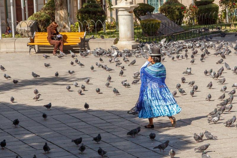 在蓝色充分走横跨拉巴斯中心广场的礼服和减速火箭的帽子的玻利维亚的妇女cholita鸽子,玻利维亚 免版税库存照片