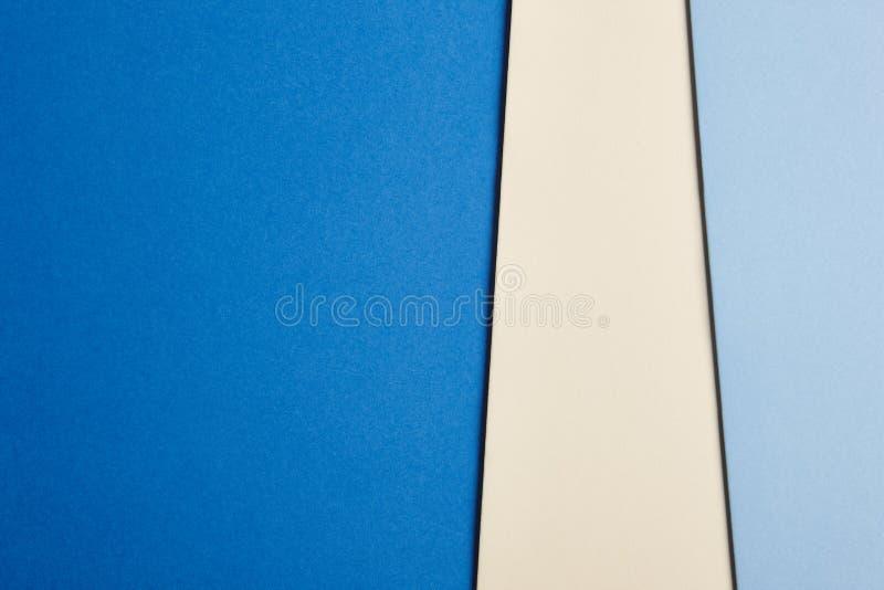 在蓝色和米黄口气的色的纸板背景 复制空间 免版税库存图片