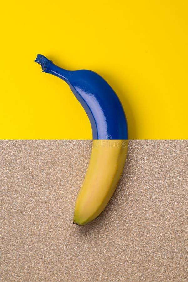 在蓝色和金子颜色明亮的背景的蓝色香蕉  图库摄影