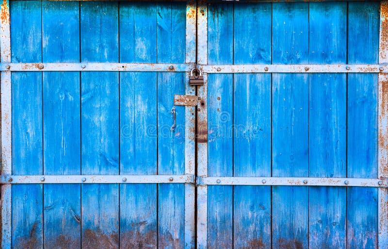 在蓝色和闭合绘的老大木门在挂锁 在锁的蓝色门 木门特写镜头 库存图片