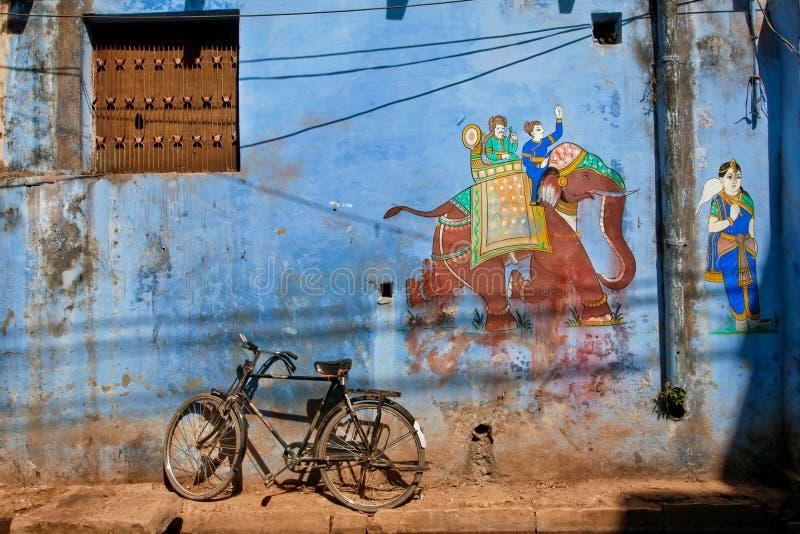在蓝色土墙壁上的老牌印地安graffitti 库存图片