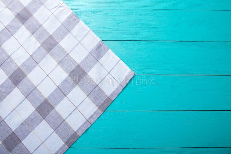 在蓝色土气木桌、顶视图和拷贝空间上的灰色格子花呢披肩桌布 嘲笑和木背景 免版税库存照片
