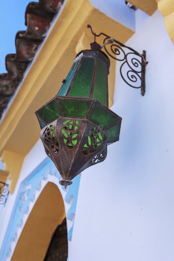 在蓝色墙壁上的绿色路灯柱 库存图片