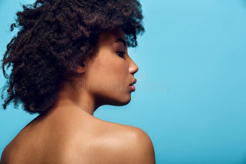 在蓝色墙壁演播室时尚photoshoot后面视图隔绝的年轻非洲妇女 免版税库存图片