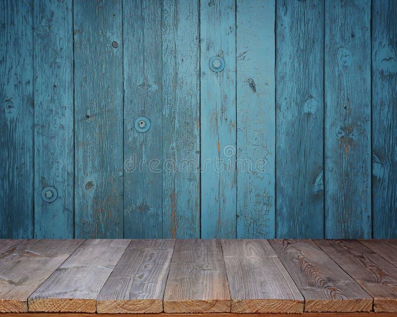 在蓝色墙壁的背景的空白的木桌 库存图片
