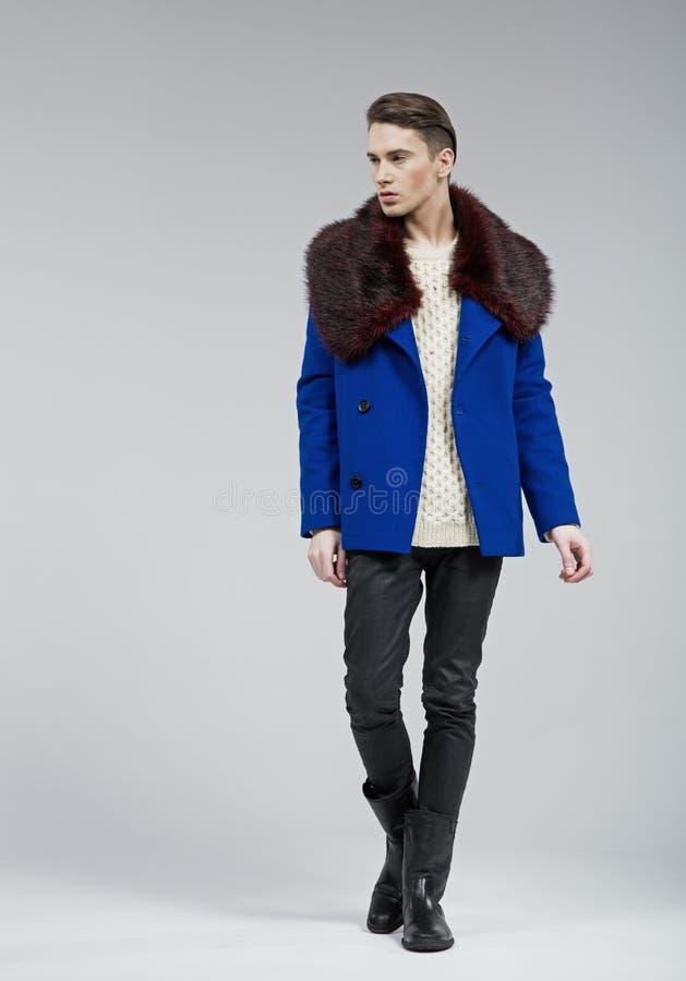 在蓝色外套打扮的英俊的年轻人 免版税库存图片