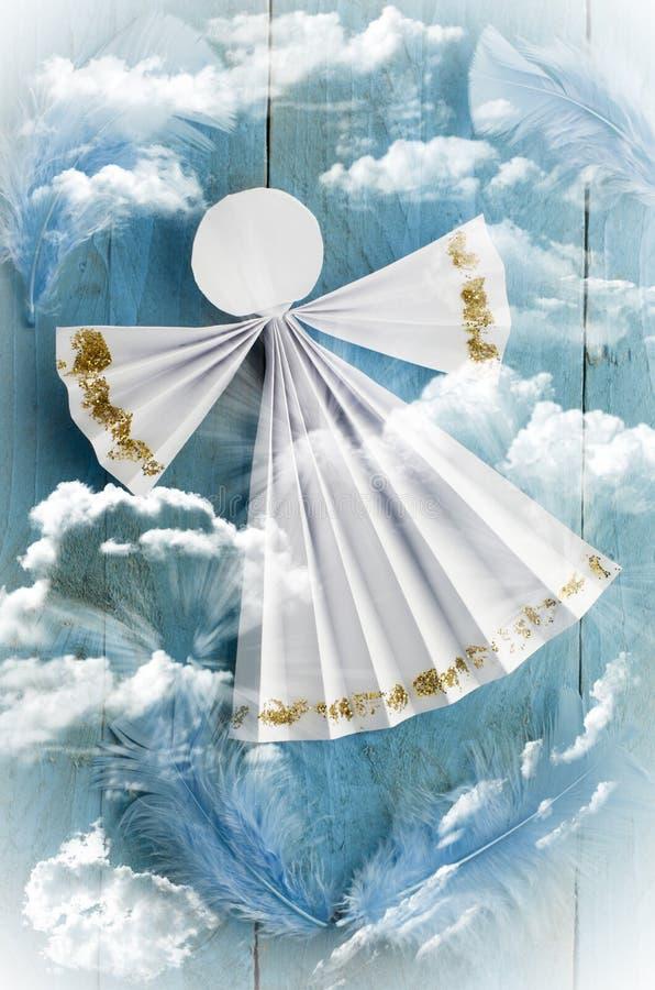 在蓝色多云背景的手工纸白色天使 图库摄影