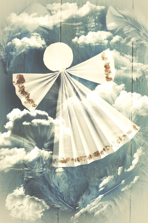 在蓝色多云背景的手工纸白色天使 库存图片