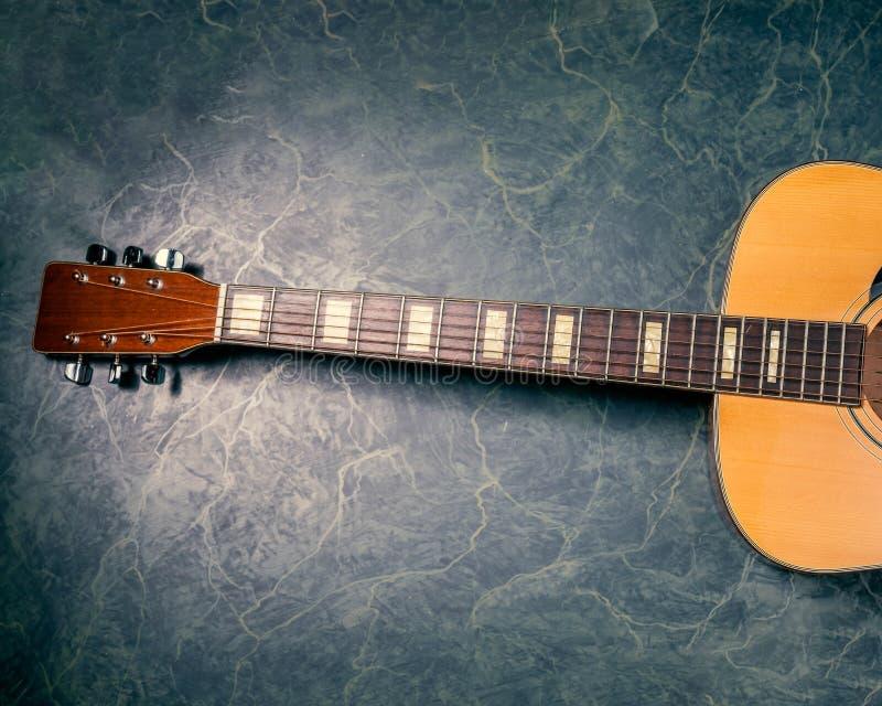 在蓝色大理石的声学吉他 库存照片