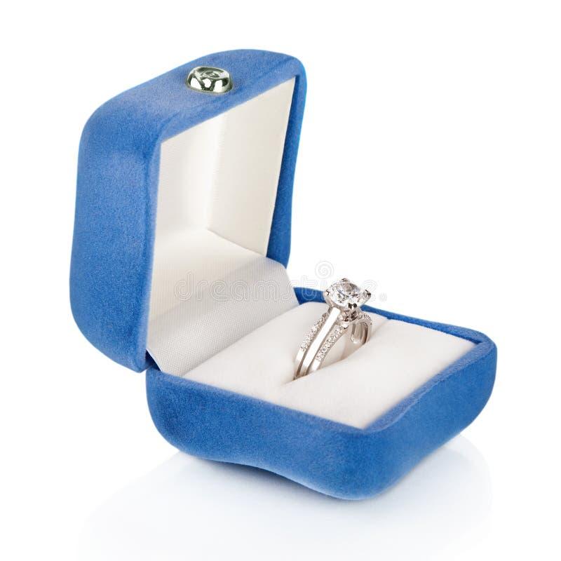 在蓝色天鹅绒丝绸配件箱的豪华钻石婚环形 库存照片