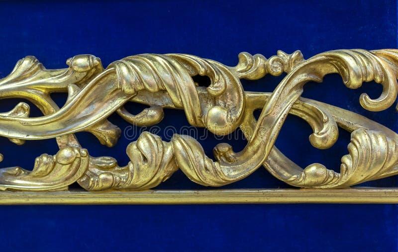 在蓝色天鹅绒背景的金黄装饰元素 库存图片