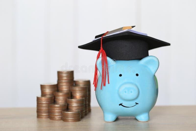 在蓝色存钱罐的毕业帽子有堆的在木背景,教育概念的攒钱的硬币金钱 库存图片