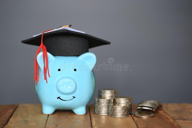 在蓝色存钱罐的毕业帽子有堆的在黑背景,教育概念的攒钱的硬币金钱 免版税图库摄影