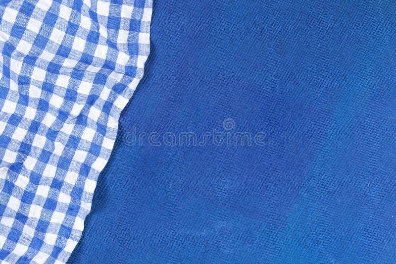 在蓝色布料背景,顶视图的蓝色方格的餐巾 图库摄影