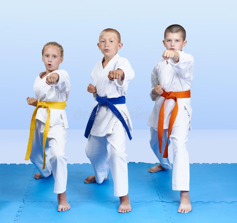 在蓝色席子三位运动员打了拳打胳膊 图库摄影