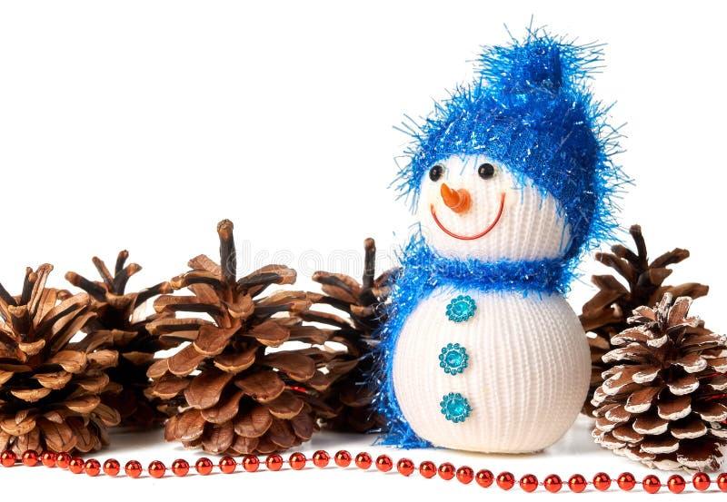 在蓝色帽子和围巾的玩具雪人有在wh隔绝的杉木锥体的 免版税库存图片