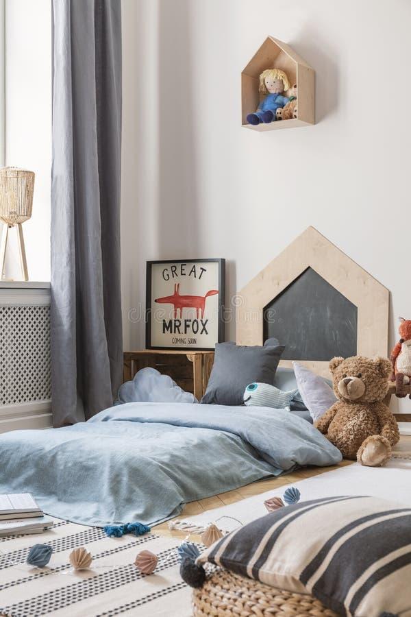 在蓝色床旁边的豪华的玩具与在孩子的卧室内部的枕头与狐狸海报和玩偶 r 免版税库存图片