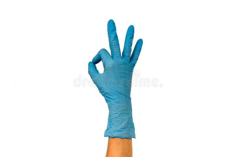 在蓝色手套的女性手显示姿态ok 在白色bac的孤立 免版税库存图片