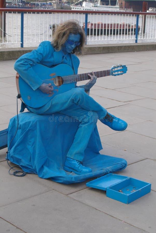 在蓝色打扮的街道艺术家 免版税库存照片