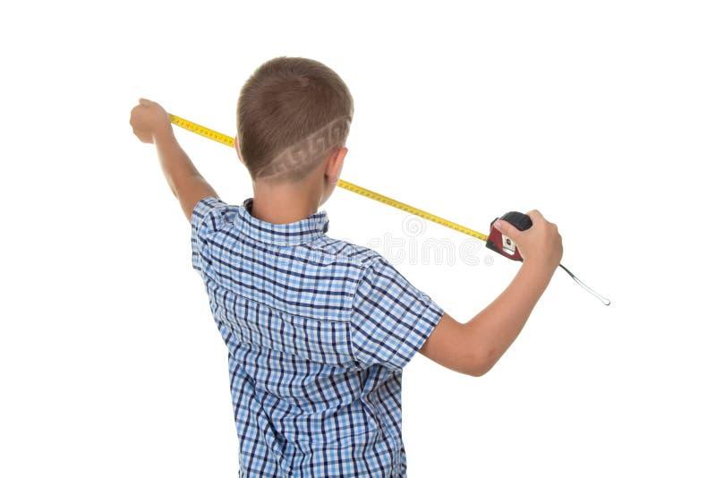 在蓝色方格的衬衣的逗人喜爱的年轻建造者测量某事与一卷测量的磁带,隔绝在白色背景 免版税库存图片