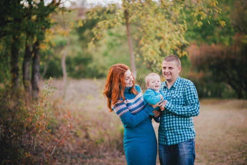 在蓝色时髦的衣裳的愉快的家庭走在秋天森林里的 免版税库存照片