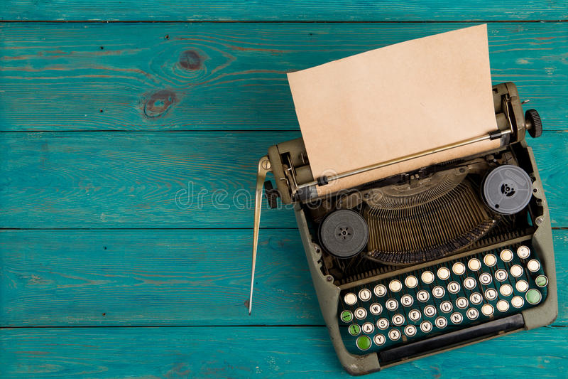 在蓝色木书桌上的打字机 库存图片