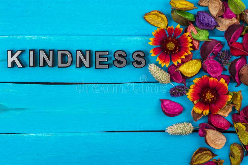 在蓝色木头的仁慈词与花 库存图片