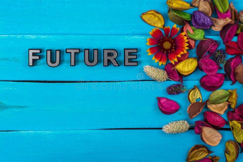 在蓝色木头的未来词与花 库存图片