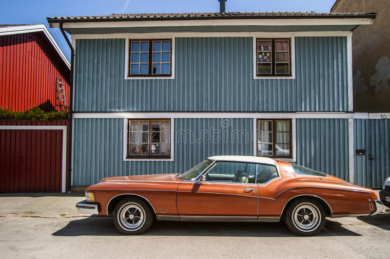 在蓝色木房子的背景的古板的红色汽车 库存照片