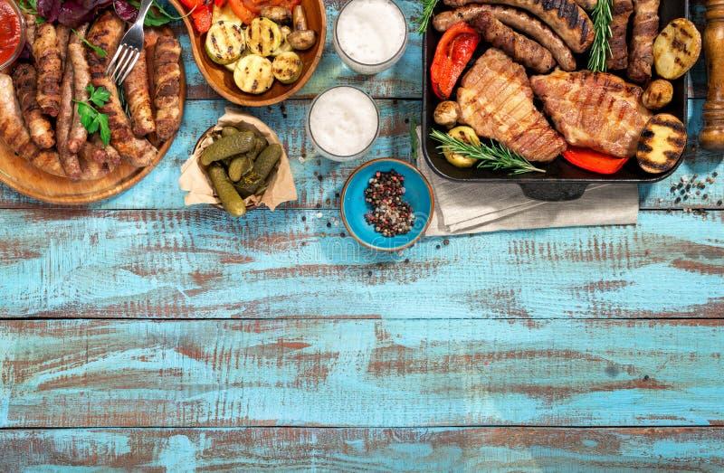 在蓝色木桌上的各种各样的烤食物与拷贝空间 库存照片