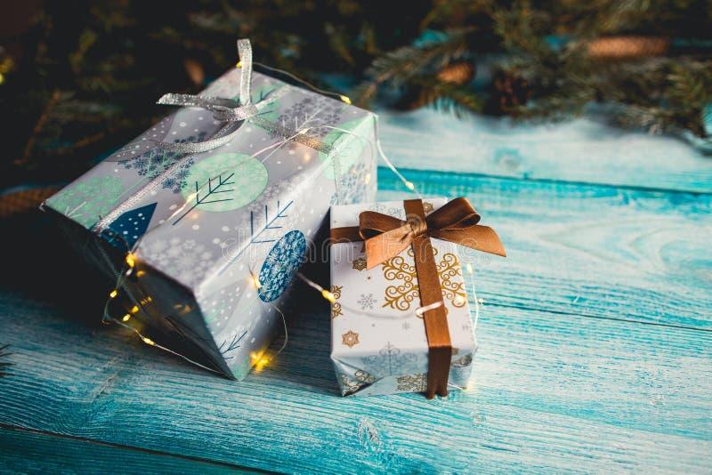 在蓝色木桌上的圣诞节礼物与冷杉小树枝 免版税图库摄影