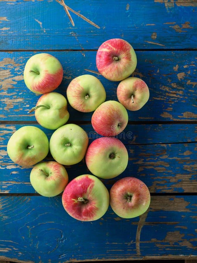 在蓝色木桌上的新鲜和成熟苹果 免版税库存图片
