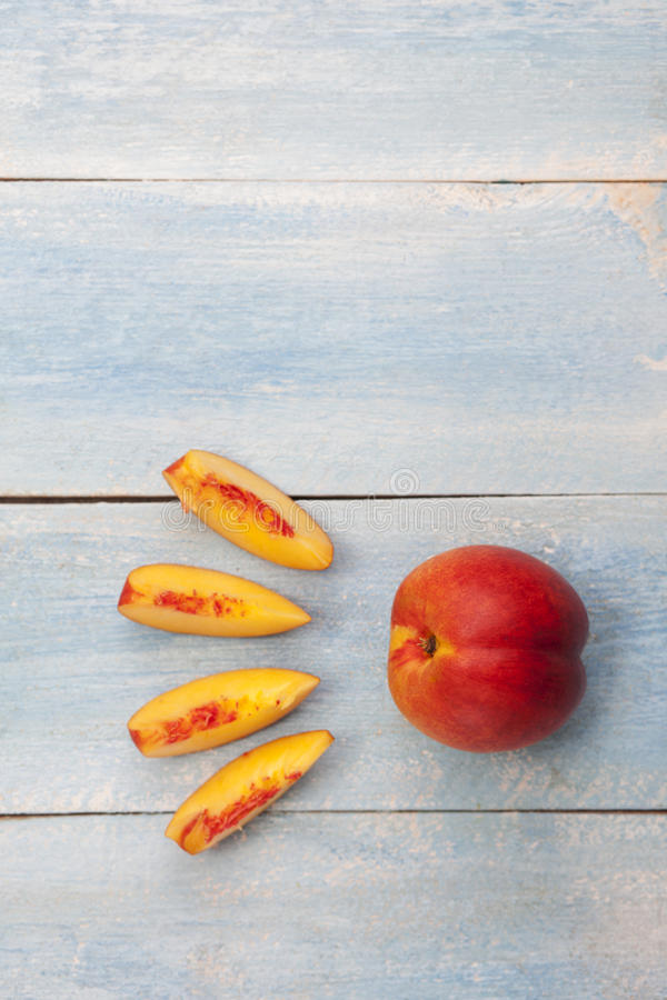 在蓝色木桌上的新鲜的切的油桃 库存图片