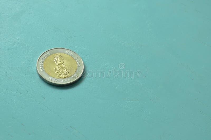 在蓝色木桌上的泰铢硬币 免版税库存照片