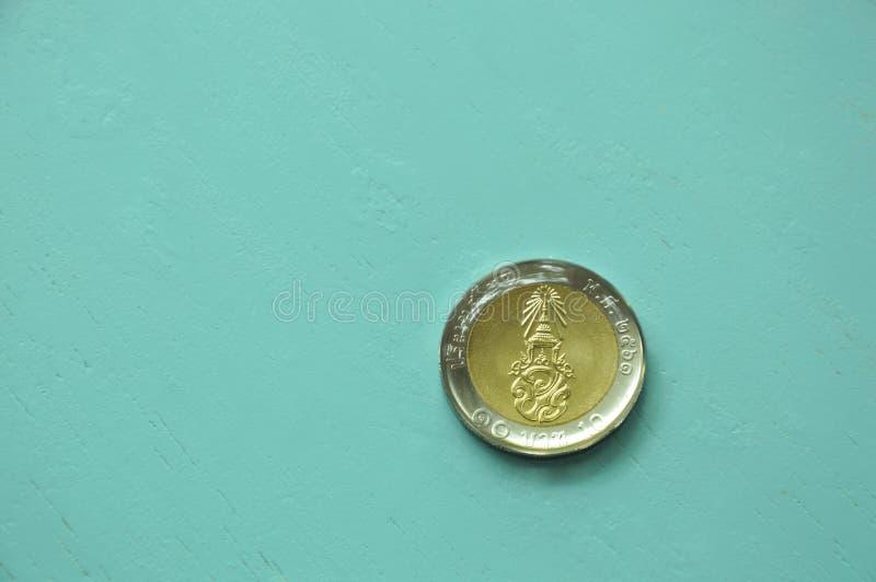 在蓝色木桌上的泰铢硬币 免版税库存图片