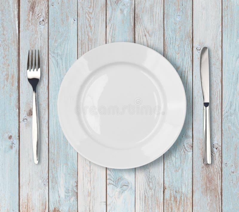 在蓝色木桌上的白色空的菜盘设置 库存图片