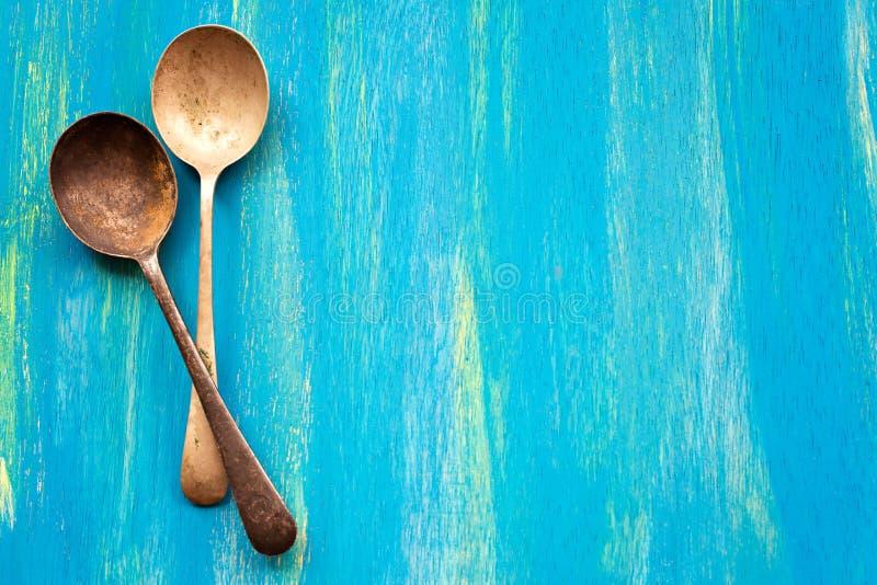 在蓝色木背景,顶视图的两把老葡萄酒匙子 库存照片