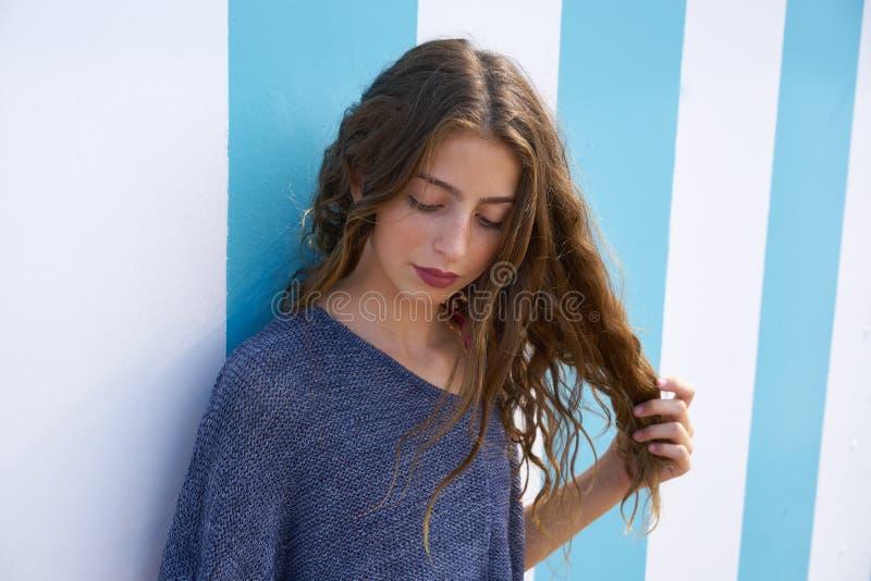 在蓝色条纹墙壁的深色的青少年的女孩画象 免版税库存照片