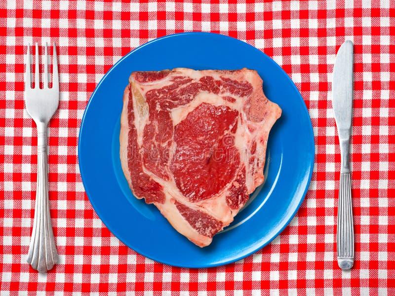 在蓝色板材的未加工的牛排 图库摄影