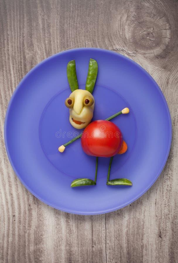 在蓝色板材的菜兔子在木背景 免版税库存图片