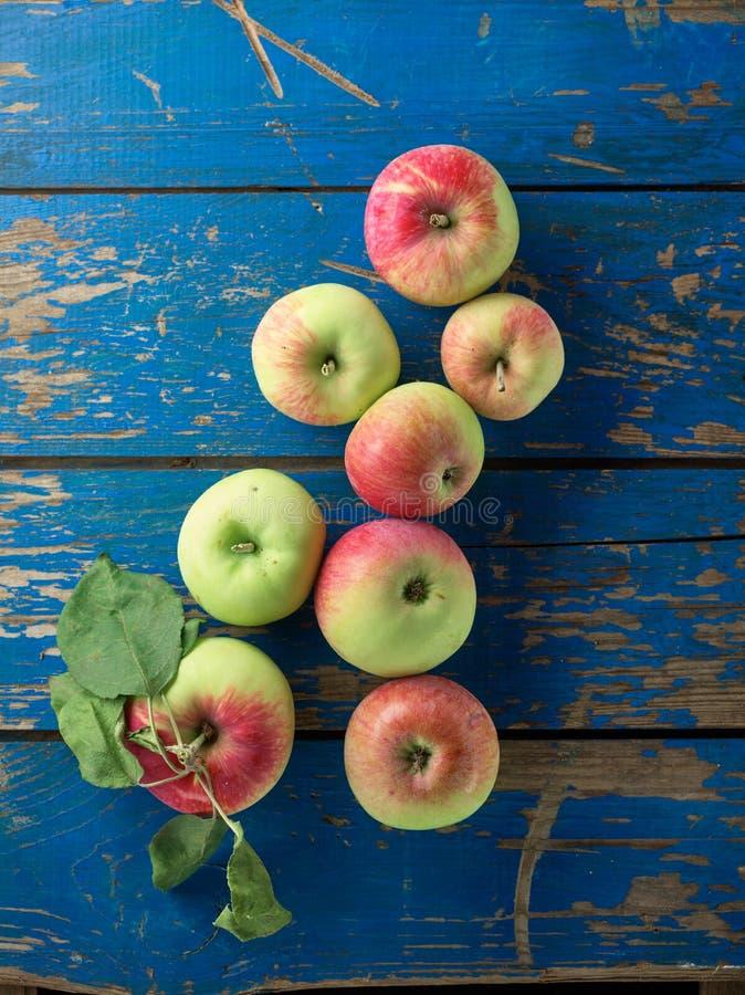 在蓝色桌上的新鲜和成熟苹果 库存图片